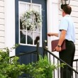 Stock Video: A door to door salesman walks up to a house and knocks on the door.
