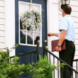 Stock Video: Door to door salesmwalks up to house and knocks on door.