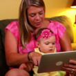 A mother uses a tablet computer with her young baby on the sofa. — Stock Video