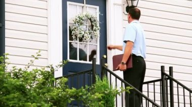 A door to door salesman walks up to a house and knocks on the door. — Stock Video