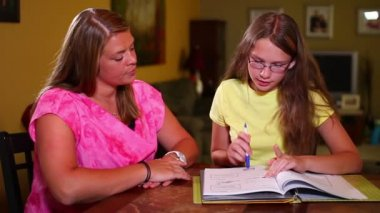 A mother helps her daughter with homework at the kitchen table. — Stock Video
