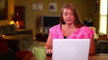 女性に座っているし、彼女のラップトップ コンピューターは台所のテーブルでの彼女のメールをチェック. — ストックビデオ