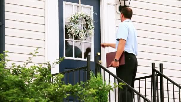 Un vendedor de puerta a puerta camina hacia una casa y llama a la puerta. — Vídeo de stock