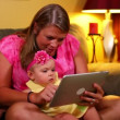 A mother uses a tablet computer with her young baby on the sofa. — Stock Video #15840273