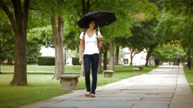 A student shares her umbrella on a college campus while walking to class.