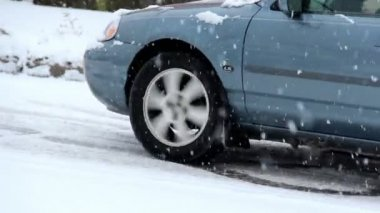A car struggles to make it up a hill during a snow storm.