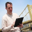 Man Uses iPad Outside - Stock Photo