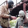 The guy with the girl in the gas masks smell the flower — Stock Video