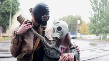The guy with the girl in the gas masks at the tram stop — Stock Video
