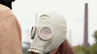 The guy with the girl in the gas masks in the industrial zone looking at each other