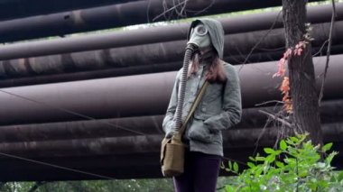 The girl in the gas mask promenade under the rain in the industrial zone — Stock Video