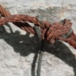 Knotted rusty steel wire against concrete wall — Stock Photo