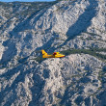 Yellow airplane flying near mountain — Stock Photo