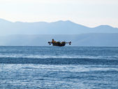 Fire figher airplane preparing to land at sea — Stock Photo