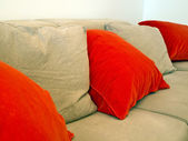 Nice sofa with red and pasteln pillows — Stock Photo