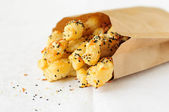 Puff pastry sticks with sesame seeds in a paper bag — Stock Photo