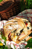 Picnic loaf stuffed with ham, black olives, tomato, egg, pickles, cheese and basil — Stock Photo