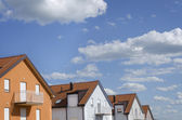 Roofs of houses under blue sky with clouds — Stockfoto