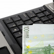 Close up of a laptop computer with couple of euro notes on the keyboard — Stock Photo