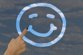 Hand drawing a smiley face on a dirty window — Stock Photo