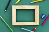Picture frame with pencil crayons — Stock Photo