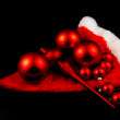 Red christmas balls and hat on black — Stock Photo