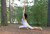 Woman in yoga one legged king pigeon pose — Stock Photo