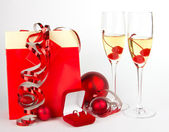 Champagne glasses with christmas presents on white — Stockfoto