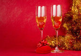 Christmas champagne glasses and present on red — Stock Photo