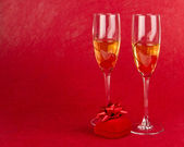 Two champagne goblets with jeweller box on red — Stock Photo