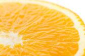 A slice of an orange fruit close on white — Stock Photo