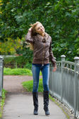 Young blond woman walking in the park — Stock Photo