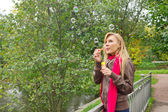 Young blond woman blowing soap bubbles in the park — Stock Photo