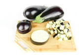 Ripe eggplant with cube cuts and slices on wood on white — Stock Photo