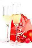 Two glass goblets with champagne, Christmas balls and present on white background — Stock Photo