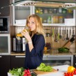 Young woman with champagne in kitchen — ストック写真