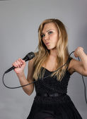 Young pretty blond woman sing in microphone — Stock Photo