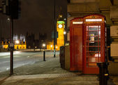 Traditional red phone booth in London with the Big Ben in the ba — Stock Photo