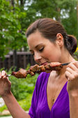 Woman enjoying barbecue outdoors — Stock Photo
