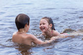 Little boy teaches his little sister to swim in a lake — Stock Photo