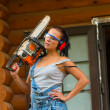 Pretty young woman builder with petrole-powered chain saw — Stock Photo