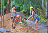 Pretty young woman builder digging a shovel — Stock Photo