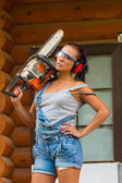 Pretty young woman builder with powered chain saw — Stock Photo