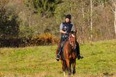 Mujer atractiva elegante montado en un caballo — Foto de Stock
