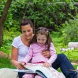 Mother and daughter read book outdoors — Stock Photo