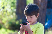 Child playing phone outdoors — Stock Photo