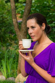 Beautiful young woman drinking coffee outdoors — Stock Photo