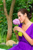 Beautiful young brunet woman with flower — Stock Photo