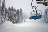 Chairlift in snowy forest — Foto Stock