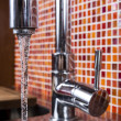 Kitchen faucet flowing — Stock Photo